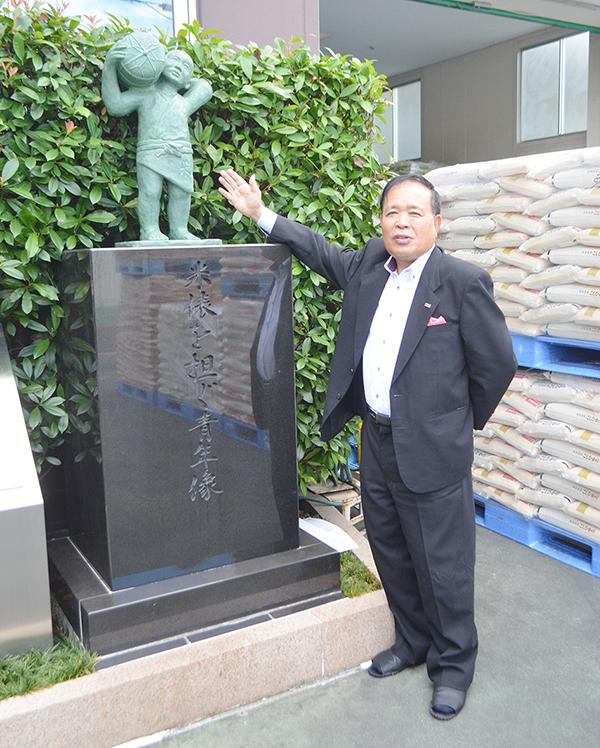 米俵を担ぐ青年の像を紹介する幸南食糧を創業した川西修会長